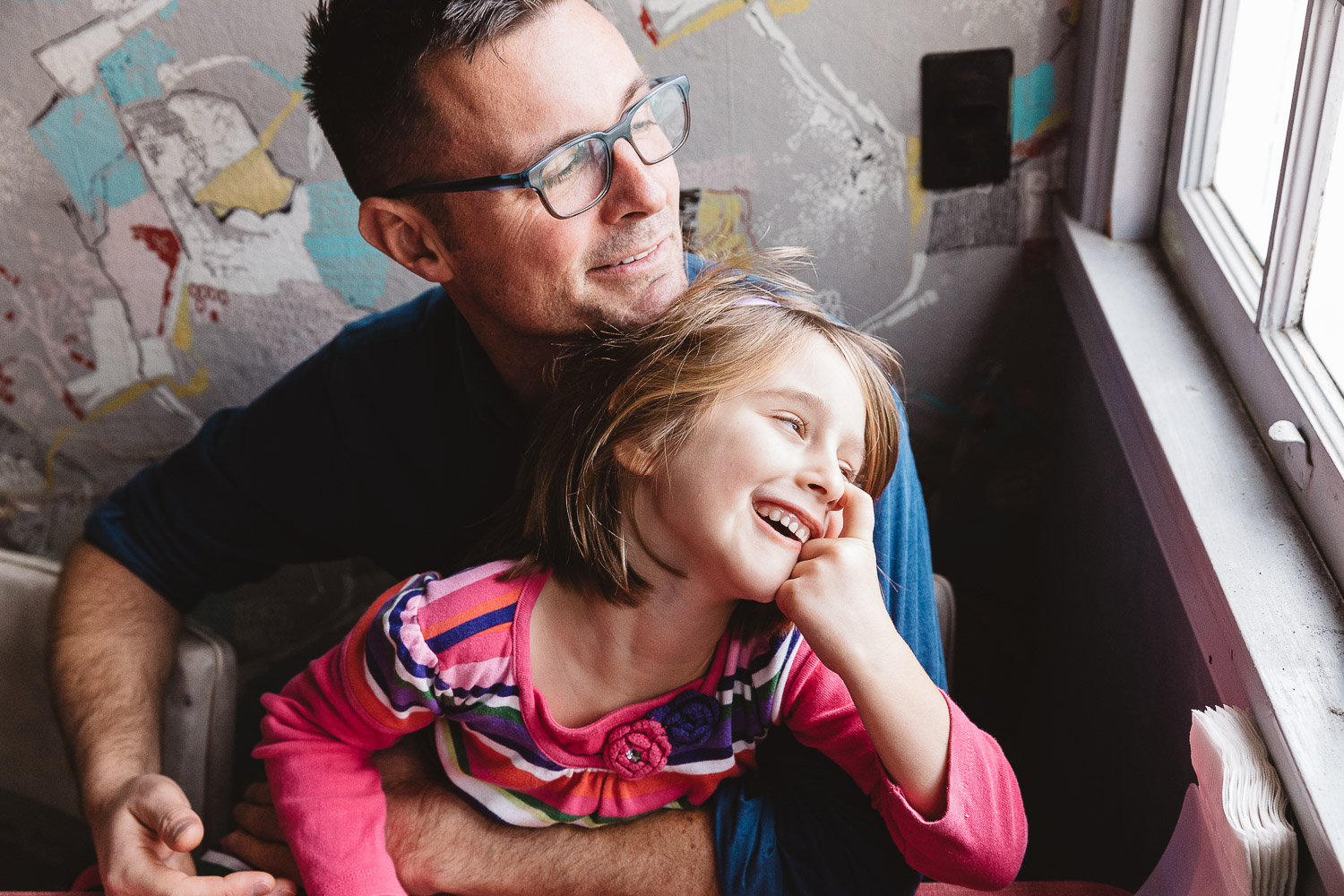 father and daughter snuggling near window smiling