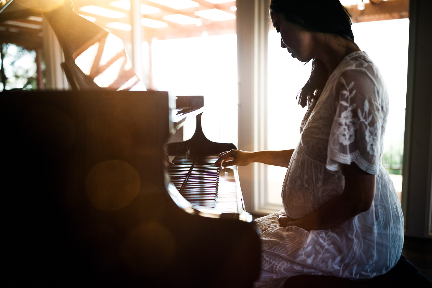 beautiful pregnant woman playing piano with warm sunlight glow