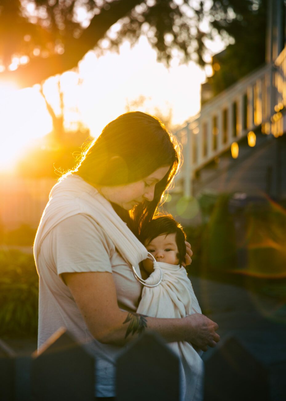 mother rocking baby girl in swaddle at sunset